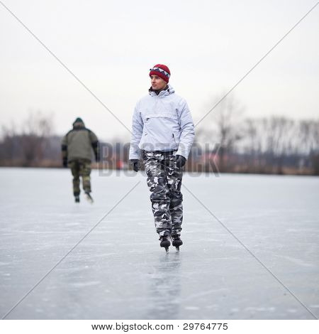 Handsome young man ice skating outdoors on a pond on a cloudy winter day (color toned image; shallow DOF)