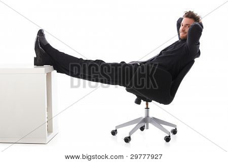Young businessman taking a break, resting with legs on desk, smiling.?