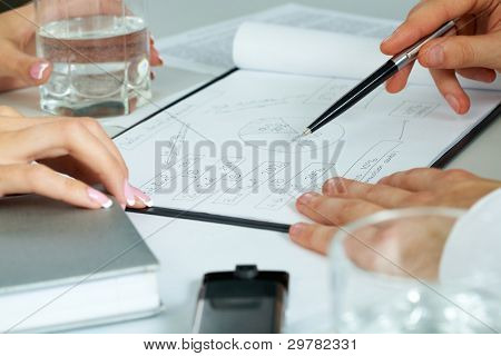 Close-up of human hands working with documents at business meeting