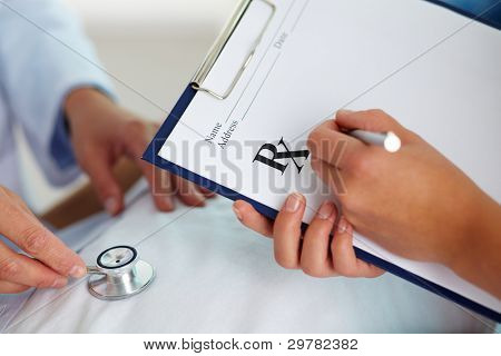 Hand of female doctor with pen writing on prescription blank