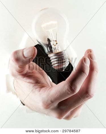 businessman hand holding a light bulb in a paper hole