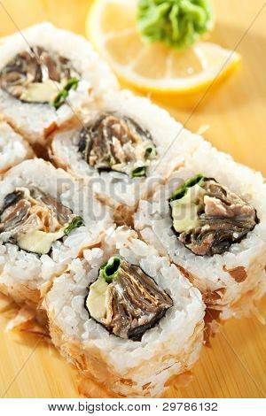 Salmon Skin Maki Sushi - Roll with Eel, Spring Onions and Avocado inside. Grilled Salmon Skin outside