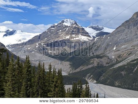 Spectacular View Of The Canadian Rockies With Glacier, Melt Water Flow And Forests Under Blue Cloudy