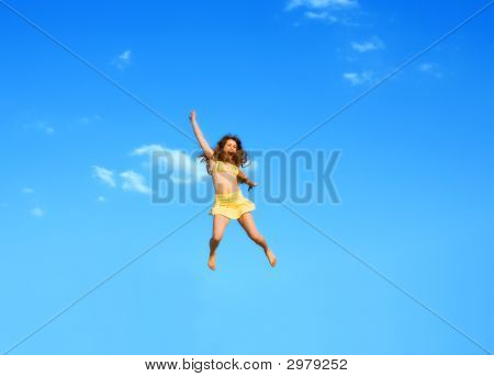 The Happy Jumping Girl On A Background Of The Blue Sky