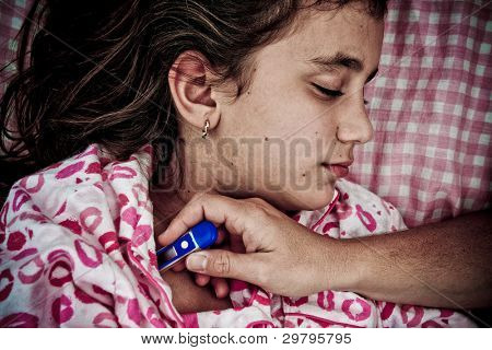 Grunge sad image of a small girl sick with fever while a hand with a thermometer measures her temperature