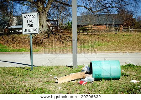 """Litter in barrel turned over next to """"no littering"""" sign"""
