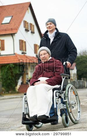 Caregiver careful man walking and embracing disabled senior woman grandmother at wheelchair in nature