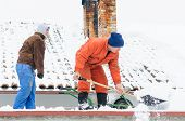 pic of diligent  - Two men diligently clean snow off the roof.