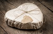 image of gift wrapped  - Heart shaped gift on a wooden background - JPG