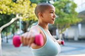 Active curvy woman using dumbbells in the park. Side view of young woman doing stretching exercise u poster