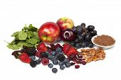Foods rich in antioxidants, isolated on white.  Includes spinach, raisins, apples, plums, red grapes