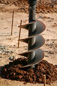 stock photo of auger  - power auger beging to dig a hole in the dirt and ground - JPG