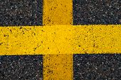 Road Marking Line With Yellow Paint On Asphalt. In The Shape Of A Cross. Marking The Motorway. Close poster