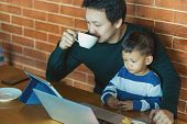 Asian Single Dad With Son Are Looking The Cartoon Via Technology Laptop And Drinking Coffee With Wor poster