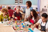 Group Of Mature Adults Attending Art Class In Community Centre With Teacher poster