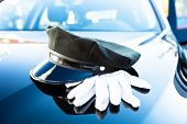 Chauffeurs Cap And Pair Of Gloves On Car Bonnet poster