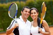 Happy couple of tennis players training outdoors