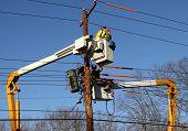 stock photo of utility pole  - Two lineman working to restore power on electrical lines - JPG
