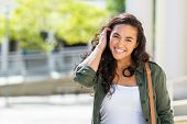 Happy young beautiful woman walking on the street. Portrait of cheerful university student looking a poster