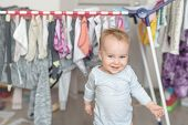 Cute Adorable Caucasian Toodler Boy Laughing And Having Fun Playing Home With Mess And Clothes Dryer poster