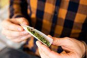 Close Up Of Addict Lighting Up Marijuana Joint With Lighter. Man Rolling A Marijuana Joint. Drug Use poster