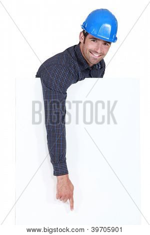 Manual worker pointing downwards at poster