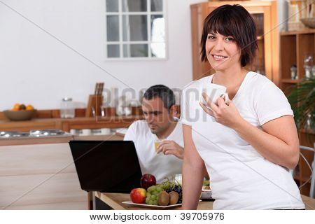 Woman drinking coffee while her husband looks at his laptop during breakfast
