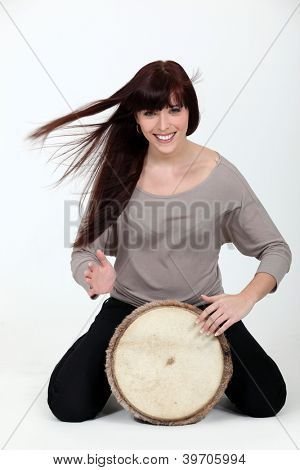 Brunette playing a bongo drum