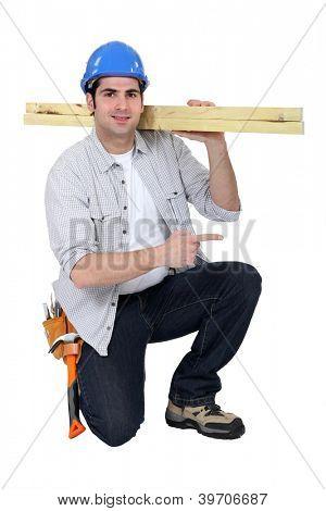 Builder carrying wood on shoulder