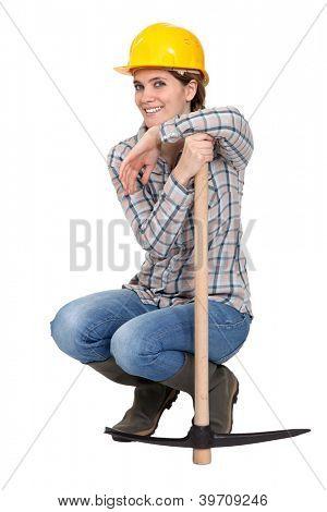Woman kneeling by a pickax