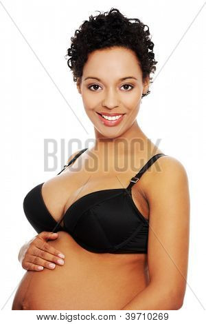 Portrait of a young smiling beautiful pregnant woman embracing her belly, isolated on a white background.
