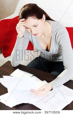 Young beautiful woman stressed because of bills.