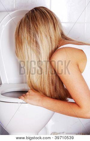 Joven rubia adolescente vomitando en el baño
