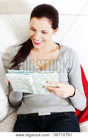 Young beautiful woman, sitting on a couch at home and having a look at a map.