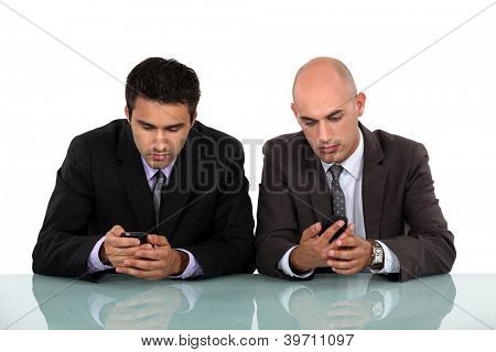 Two businessmen sending text messages