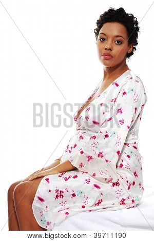 Pregnant woman sitting on bed, isolated on white background