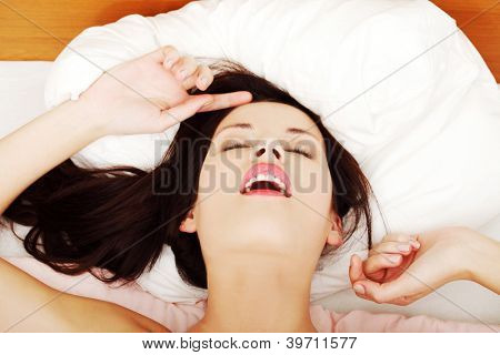 Young naked woman in bed getting orgasm.