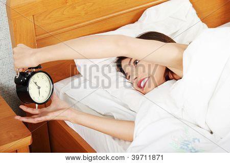 Sleepy woman in morning trying to turn off alarm clock