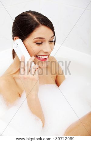Bella joven hablando por teléfono celular mientras toma un baño