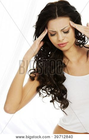 Young woman holding her head in pain suffering from a headache,migraine, stress, insomnia or hangover