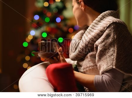 Young Woman Sitting Chair With Hot Beverage In Front Of Christmas Tree. Rear View