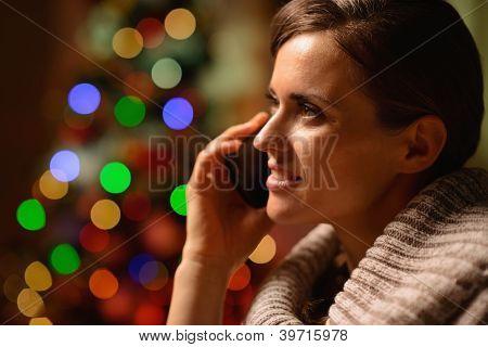 Jovem mulher sentada cadeira e fazer chamada de telefone na frente de Chri
