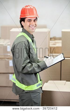 Portrait of young supervisor writing notes at warehouse