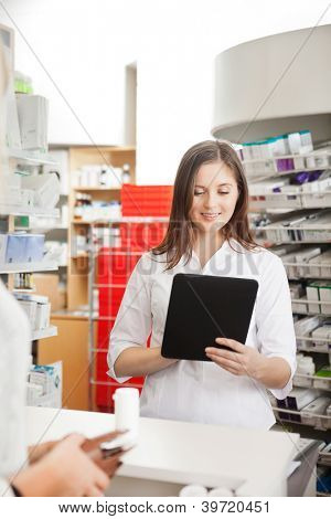 Young pharmacist with digital tablet computer helping customer