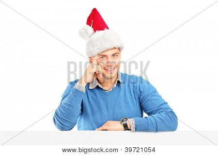 A smiling male wearing a santa hat and posing behind a blank panel isolated on white background