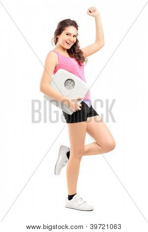 Full length portrait of a young happy female holding a weight scale isolated on white background