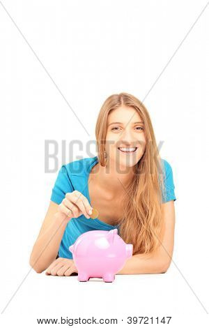 Smiling female putting a coin into a piggy bank isolated against white background