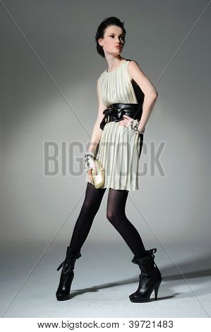 Studio portrait of a young woman with a purse posing on light background
