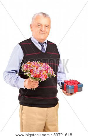 A smiling mature man holding a gift and a bouquet of flowers isolated on white background