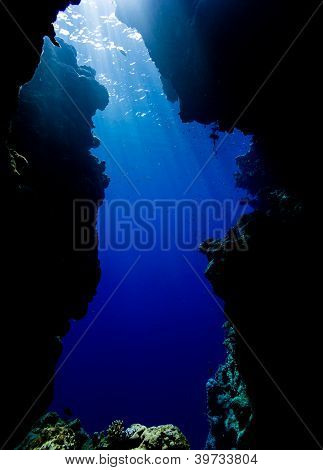 Sun Rays Filter Down Through Blue Water At The Exit From A Sea Cavern
